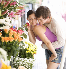 A young couple looking at a flower stall