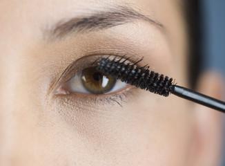 A young woman applying mascara