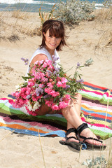 beautiful young woman holding flowers sitting on the beach