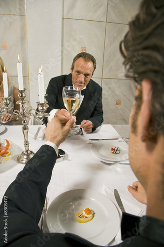 Mature man with his friend toasting with wine glasses
