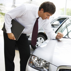 A car salesman polishing a car