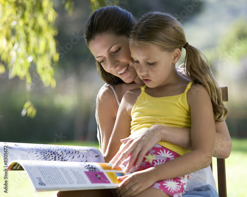 A woman and young girl sitting in the garden reading a book