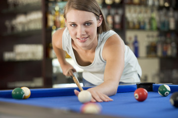 A teenage girl playing pool