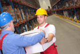 worker in uniform deliverying box to another in warehouse poster