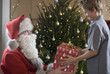 Father Christmas/Santa Claus offering a present to a young boy