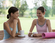 Two young women drinking coffee after a yoga class