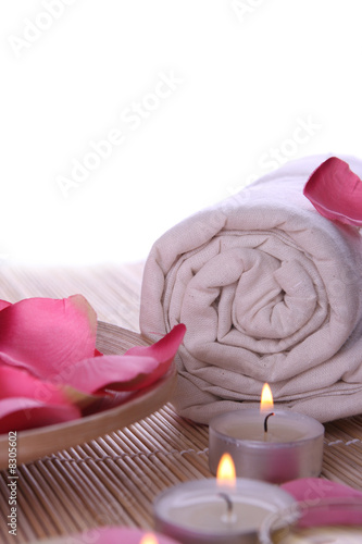 spa products with rose petals, oil container, towel and candles - 8305602