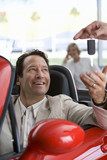 Salesman handing key to satisfied male customer sitting in red convertible in car showroom, smiling