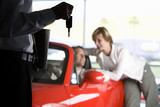 Couple looking at red convertible in car showroom, focus on salesman holding key in foreground