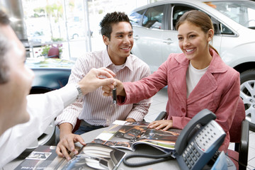 Young couple sitting at desk in car showroom, salesman handing key to woman, smiling
