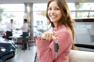 Salesman shaking hands with customer in car showroom, focus on woman holding car key in foreground