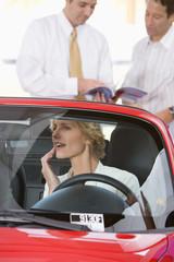 Woman sitting in red convertible in car showroom, watching salesman showing man brochure in mirror