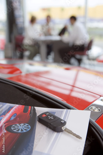 Salesman talking to customers in car showroom, focus on car key and photograph in foreground