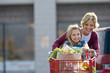 Mother and daughter (7-9) pushing shopping trolley in supermarket car park, smiling, front view, portrait