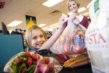 Mother and daughter (7-9) placing items on checkout conveyor belt in supermarket, smiling, portrait
