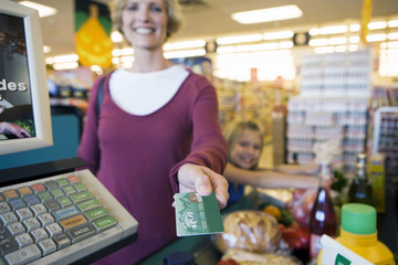 Girl (7-9) placing items on checkout conveyor belt in supermarket, mother paying with credit card, smiling