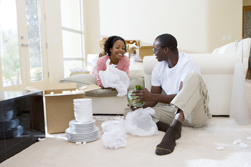 Couple moving house, woman lying on living room sofa, man unpacking glassware from box, smiling