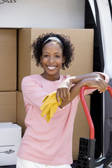 Woman moving house, standing beside van in driveway, leaning on hand dolly, smiling, portrait