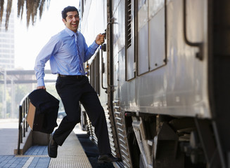 Late businessman hurrying to catch passenger train, leaping onto train with briefcase, smiling, portrait