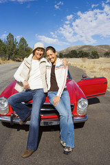 Mature woman and adult daughter standing in front of red convertible car on country road, smiling, front view, portrait