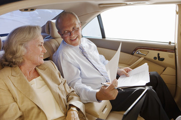 Senior businessman and woman sitting in back-seat of car, man showing woman document, smiling, side view