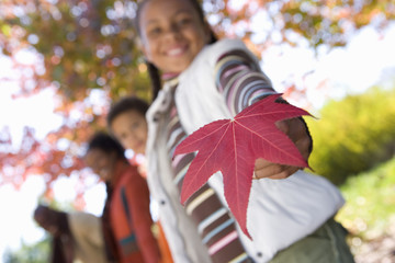 Family walking in autumn park, focus on girl (7-9) holding red maple leaf, smiling, low angle view, portrait (tilt)