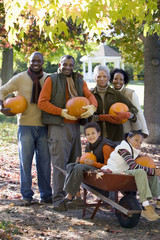 Multi-generational family standing in autumn garden, holding pumpkins, children (7-9) in wheelbarrow, portrait