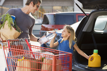 Father and daughter (7-9) loading car boot with groceries in supermarket car park, smiling, side view