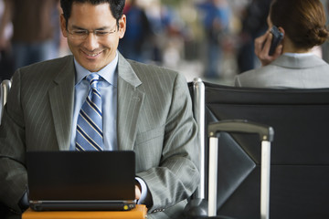 Businessman sitting in airport terminal, using laptop, smiling, front view