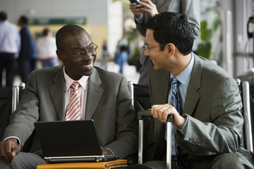 Two businessmen sitting in airport terminal, man using laptop, talking, front view