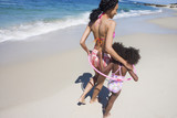 Mother and daughter (6-8) walking along sandy beach near water's edge, arms around each other, rear view