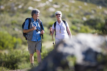 Mature couple hiking on mountain trail, carrying rucksacks, woman using hiking pole, front view