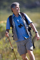 Mature man hiking on mountain trail, carrying rucksack, using hiking pole, front view (tilt)