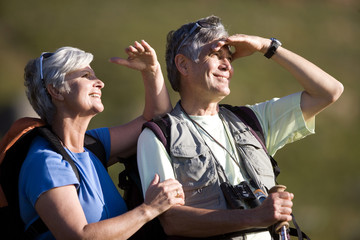 Mature couple hiking on mountain trail, looking at scenery, shielding eyes from sunlight, smiling, side view