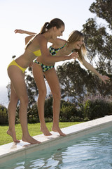 Two teenage girls having fun by a pool