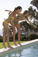 Two teenage girls having fun by a pool