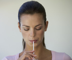 Woman drinking through a straw