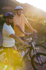 Mature couple standing with bicyles on mountain trail in bright sunlight, looking at scenery (lens flare)