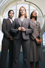 Three confident businesswomen, in grey suits, standing in lobby, front view, portrait