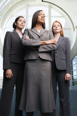 Three confident businesswomen, in grey suits, standing in lobby, front view, portrait, low angle view