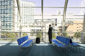 Solitary businessman waiting in airport departure lounge, looking through large window at urban scene, rear view