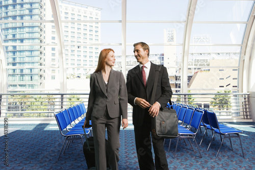 Businessman and woman walking with luggage in tow in airport departure lounge, smiling, front view