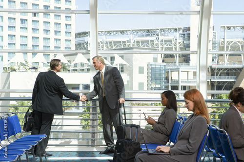 Two businessmen shaking hands beside large window in airport departure lounge, other passengers waiting in seats, side view