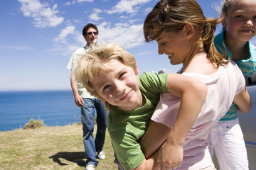 Mother embracing son and daughter (7-9) on clifftop overlooking Atlantic Ocean, father looking on
