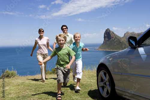 Family running towards parked car on clifftop overlooking Atlantic Ocean, smiling, portrait