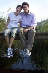Couple sitting on small wooden footbridge above stream, arms around each other, smiling, front view, portrait