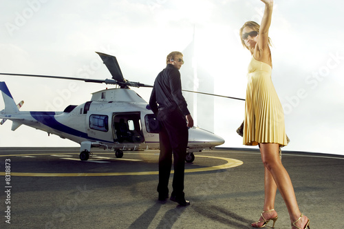 A man and woman getting on board a helicopter