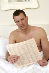 Young man in bed, reading papers