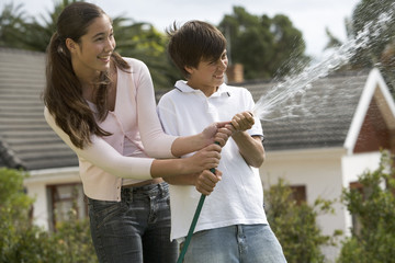 A brother and sister playing with a hose pipe