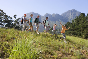 Multi-generational family hiking on mountain trail, walking in line, boy (8-10) leading, side view